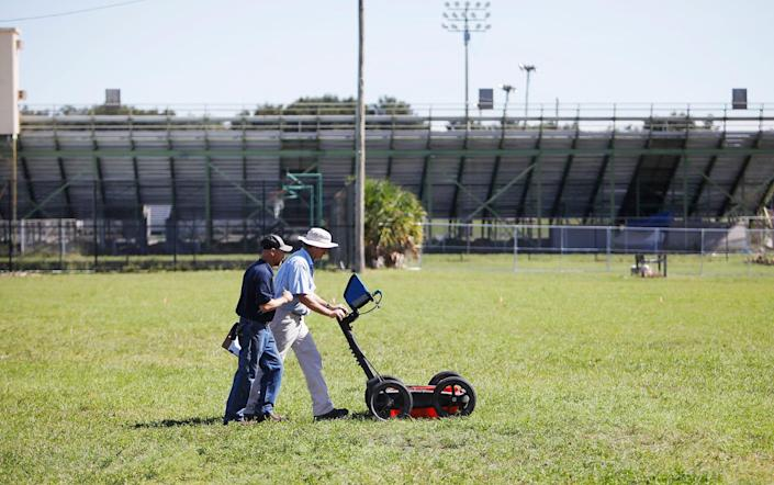 Scott Purcell, a senior geophysicist with GeoView, left, and Mike Wightman, president of GeoView use ground penetrating radar technology to scan a portion of King High School campus in search for Ridgewood Cemetery in Tampa, Florida on Wednesday, October 23, 2019.