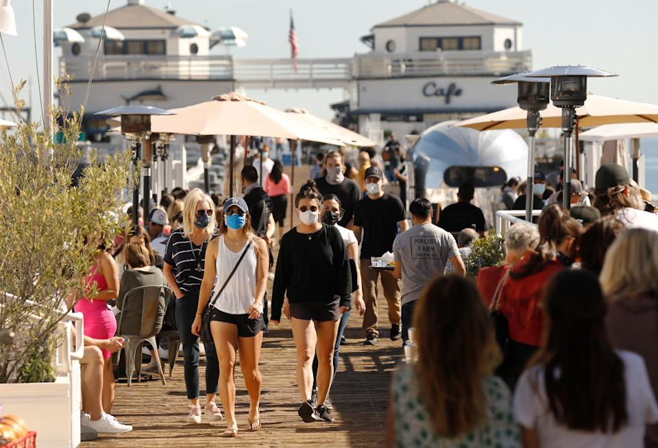 A crowded boardwalk in Los Angeles filled with people wearing face masks.