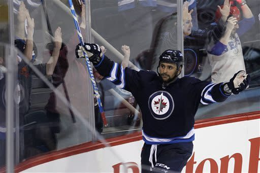 Winnipeg Jets' Dustin Byfuglien (33) celebrates winning goal against the Carolina Hurricanes in overtime of their NHL hockey game in Winnipeg, Manitoba, Thursday, April 18, 2013. The Jets won 4-3. (AP Photo/The Canadian Press, John Woods)