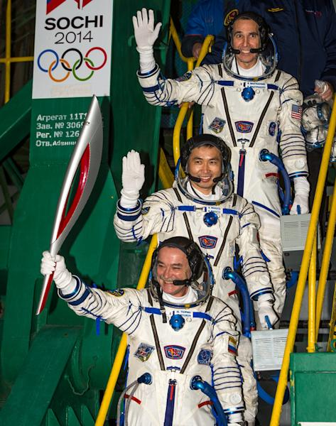 Russian cosmonaut Mikhail Tyurin, Expedition 38 Soyuz commander, holds the Olympic torch as Flight Engineer Koichi Wakata of Japan and Rick Mastracchio of NASA (top) wave farewell prior to boarding the Soyuz TMA-11M rocket for launch, Thursday,