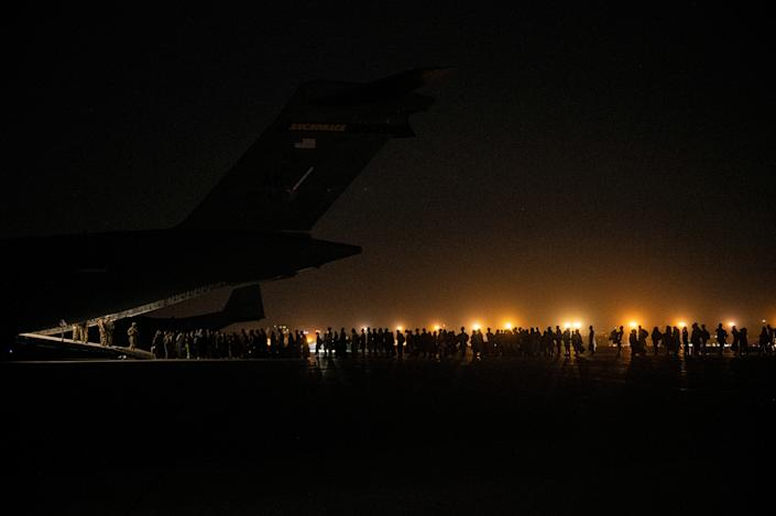 Evacuees from Afghanistan board a military aircraft during an evacuation from Kabul, in this photo taken on August 19, 2021 at undisclosed location and released on August 20, 2021.  (Staff Sgt. Brandon Cribelar/U.S. Marine Corps/Handout via Reuters)