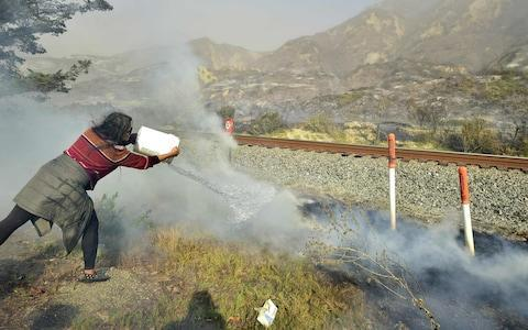 <span>Songsri Kesonchampa tosses a bucket of water on to burning embers across the road from her home </span> <span>Credit: AFP </span>