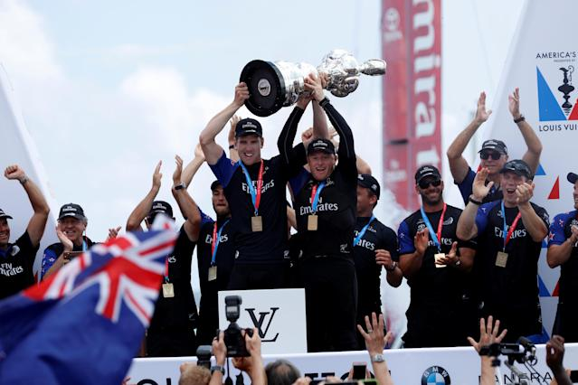 Sailing - America's Cup finals - Hamilton, Bermuda - June 26, 2017 - Peter Burling, Emirates Team New Zealand Helmsman celebrates with Skipper Glenn Ashby celebrates as they hold the America's Cup trophy after defeating Oracle Team USA. REUTERS/Mike Segar TPX IMAGES OF THE DAY