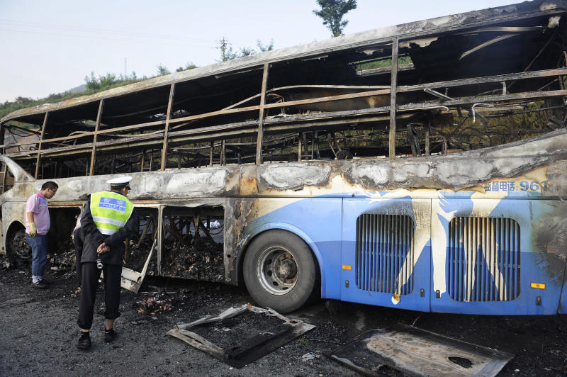 A policeman looks at a burnt-off bus after it collided with a tanker on an expressway in Yan'an in northwest China's Shaanxi province Sunday, Aug. 26, 2012. The double-decker sleeper bus rammed into the tanker loaded with highly-flammable methanol on a northern Chinese highway on Sunday, causing both vehicles to burst into flames and killing 36 people, state media said. (AP Photo) CHINA OUT