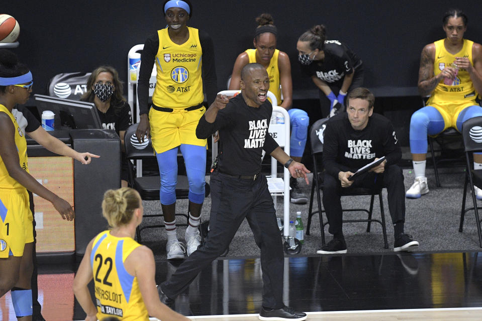 "Chicago Sky players on the bench in yellow jerseys with coach James Wade pumping his fist in a ""Black Lives Matter"" T-shirt."