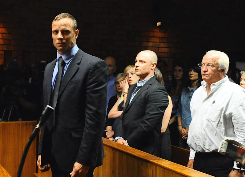 Olympian Oscar Pistorius, foreground, stands following his bail hearing, as his brother Carl, centre, and father Henke, right, look on, in Pretoria, South Africa, Tuesday, Feb. 19, 2013. Pistorius fired into the door of a small bathroom where his girlfriend was cowering after a shouting match on Valentine's Day, hitting her three times, a South African prosecutor said Tuesday as he charged the sports icon with premeditated murder. The magistrate ruled that Pistorius faces the harshest bail requirements available in South African law. He did not elaborate before a break was called in the session. (AP Photo-Masi Losi-Pretoria News) SOUTH AFRICA OUT