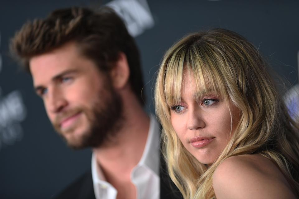 """US singer Miley Cyrus and Australian actor Liam Hemsworth arrive for the World premiere of Marvel Studios' """"Avengers: Endgame"""" at the Los Angeles Convention Center on April 22, 2019 in Los Angeles. (Photo by VALERIE MACON / AFP)        (Photo credit should read VALERIE MACON/AFP/Getty Images)"""
