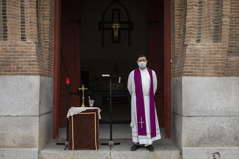 SPAIN: A priest wearing a face mask waits in front the cemetery chapel in Madrid.