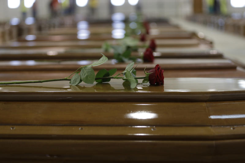 Laid roses sit on coffins of the dead migrants inside a hangar of Lampedusa's airport, Italy, Saturday, Oct. 5, 2013. A ship carrying African migrants towards Italy sank Thursday after a fire was set onboard to attract attention of any passing boats or people on shore when they ran into trouble. They had traveled for two full days and thought they had reached safety when they saw the lights of Lampedusa. Instead, at least 111 drowned and 155 survived, some of whom were in the water for three hours, clinging to anything buoyant, even empty water bottles. (AP Photo/Luca Bruno)