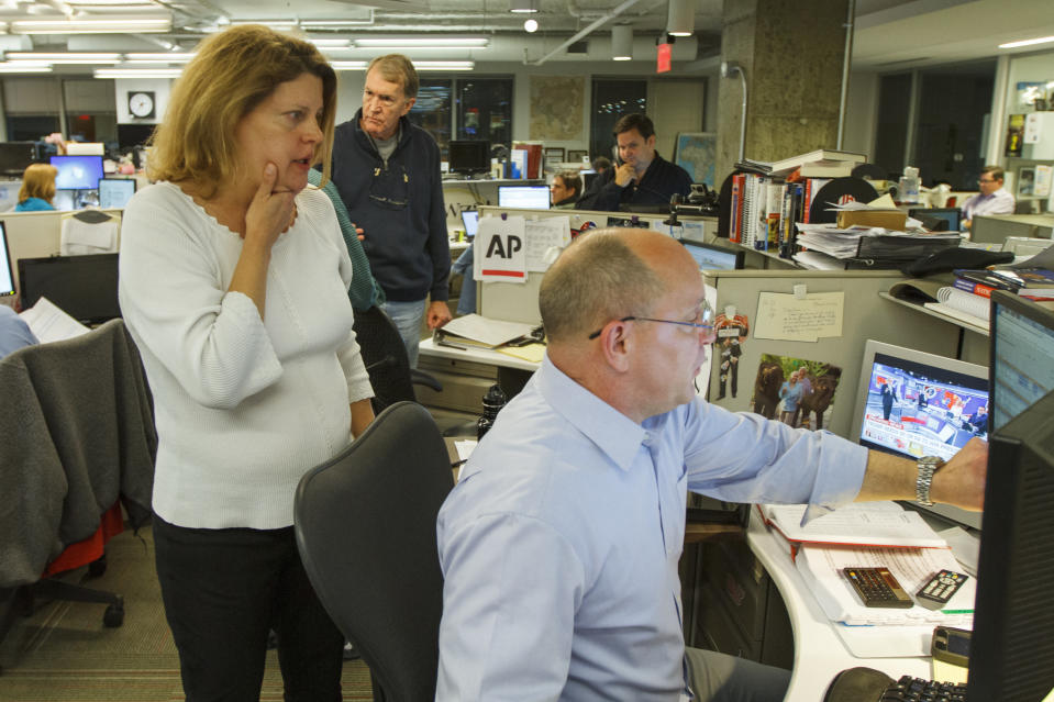 Then-Associated Press Washington bureau chief Sally Buzbee, talks with Stephen Ohlemacher, who in 2020 is the decision desk editor, in the early morning hours of Wednesday, Nov. 9, 2016, at the Washington bureau of The Associated Press during election night. (AP Photo/Jon Elswick)