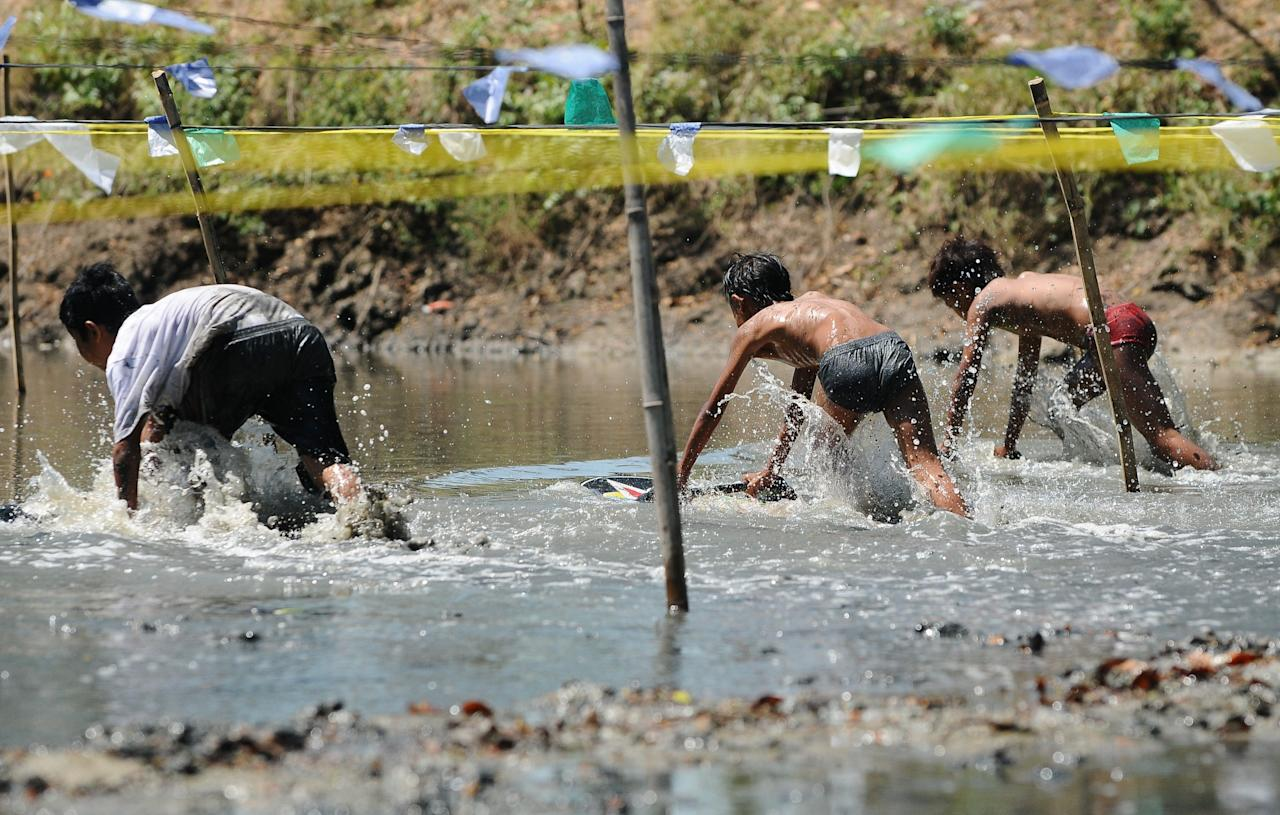 PASURUAN, JAVA, INDONESIA - AUGUST 15: Skylot participants compete in aqueous mud arena on August 15, 2013 in Pasuruan, Java, Indonesia. Skylot is a traditional mud surfing competition from Lekok Village, Pasuruan, played by clam seekers and fishermen in thanksgiving for the sea harvest. (Photo by Robertus Pudyanto/Getty Images)