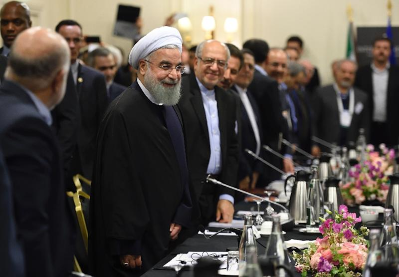 Iranian President Hassan Rouhani (C) attends a meeting with French ministers and representatives of the Movement of the Enterprises of France (MEDEF) in Paris on January 27, 2016 (AFP Photo/Eric Feferberg)