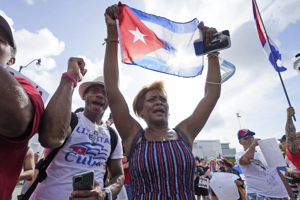 Dulce Diaz, center, and her brother Carlos Diaz, left, demonstrate, Wednesday, July 14, 2021, in Miami's Little Havana neighborhood, as people rallied in support of antigovernment demonstrations in Cuba. (AP Photo/Wilfredo Lee)