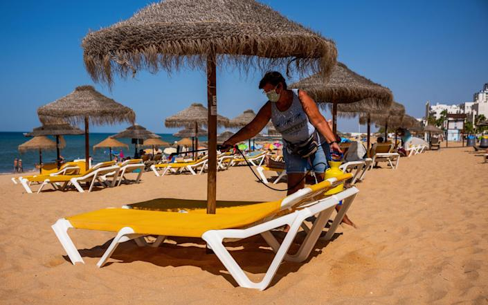 A worker wearing a protective face mask sprays disinfectant on sun loungers at Quarteira Beach in the Algarve - BLOOMBERG