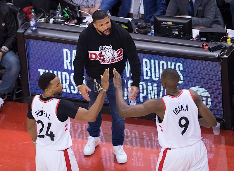 Toronto Raptors forward Norman Powell (24) and center Serge Ibaka (9) celebrate with Drake, center, during the second half of Game 4 of the team's NBA basketball playoffs Eastern Conference finals against the Milwaukee Bucks, Tuesday, May 21, 2019, in Toronto. (Nathan Denette/The Canadian Press via AP)