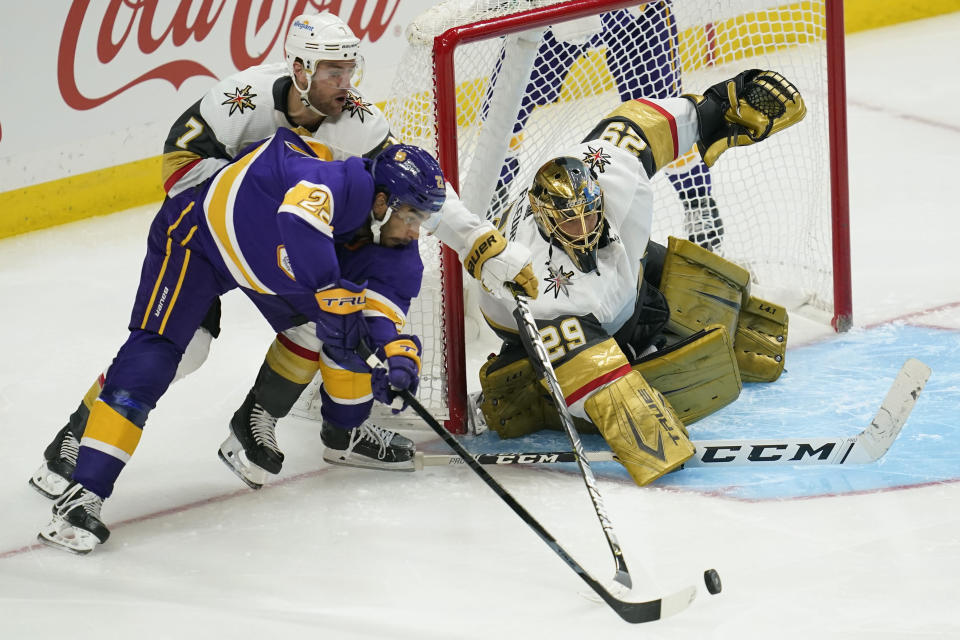 Los Angeles Kings left wing Andreas Athanasiou (22), defenseman Alex Pietrangelo (7) and goaltender Marc-Andre Fleury (29) reach for the puck during the third period of an NHL hockey game Wednesday, April 14, 2021, in Los Angeles. (AP Photo/Ashley Landis)