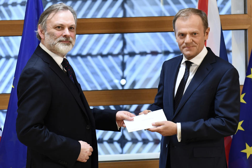 FILE - In this Wednesday, March 29, 2017 file photo, EU Council President Donald Tusk, right, receives British Prime Minister Theresa May's formal notice to leave the bloc, under Article 50 of the EU's Lisbon Treaty, from UK Permanent Representative to the EU Tim Barrow in Brussels. Britain and the European Union have struck a provisional free-trade agreement that should avert New Year chaos for cross-border traders and bring a measure of certainty for businesses after years of Brexit turmoil. (Emmanuel Dunand, Pool via AP, File)