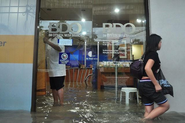 A BDO branch's entrance is shattered and is seen flooded. Majority of the metro is flooded due to heavy rains from the previous night, seen near SM Sta. Mesa, Manila, on 07 August 2012. (George Calvelo, NPPA Images)