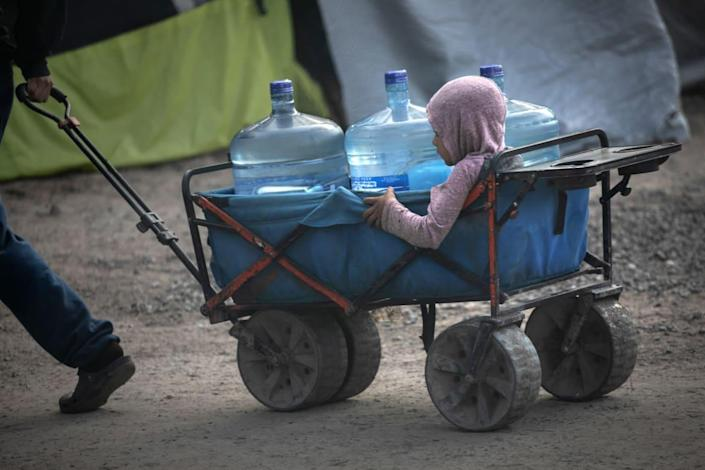"""<div class=""""inline-image__caption""""><p>Asylum seekers carry fresh water distributed at a migrant camp at the U.S.-Mexico border on Feb. 23, 2021.</p></div> <div class=""""inline-image__credit"""">John Moore/Getty</div>"""