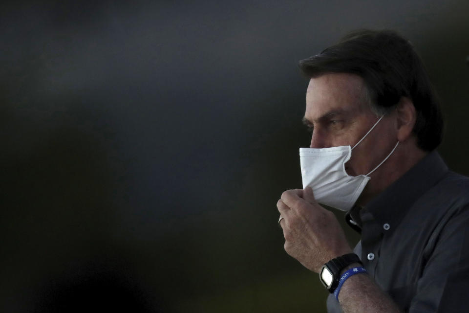 Brazil's President Jair Bolsonaro who is infected with COVID-19, adjust his protective face mask during a Brazilian flag retreat ceremony outside his official residence the Alvorada Palace, in Brasilia, Brazil, Monday, July 20, 2020. (AP Photo/Eraldo Peres)