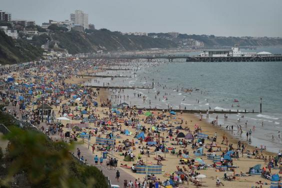 Beachgoers enjoy the sunshine as they sunbathe and play in the sea on Bournemouth beach (Getty Images)
