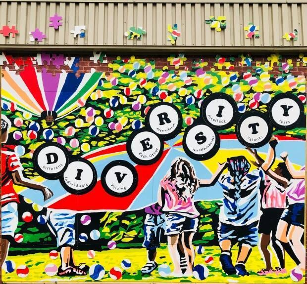 Artist and former teacher Bonny Hill designed this mural to send a message about diversity and inclusion at Sussex Elementary School. (Bonny Hill/Submitted - image credit)
