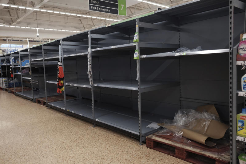 Empty shelves as toilet roll is sold out, in an Asda store in London, Sunday March 8, 2020. Fears surrounding the new spreading virus have created legions of hoarders who are stockpiling canned goods, frozen dinners, toilet paper, and cleaning products. Many want to be prepared as they watch a growing number of companies like Twitter, Microsoft and Amazon ask their employees to work from home. (Yui Mok/PA via AP)