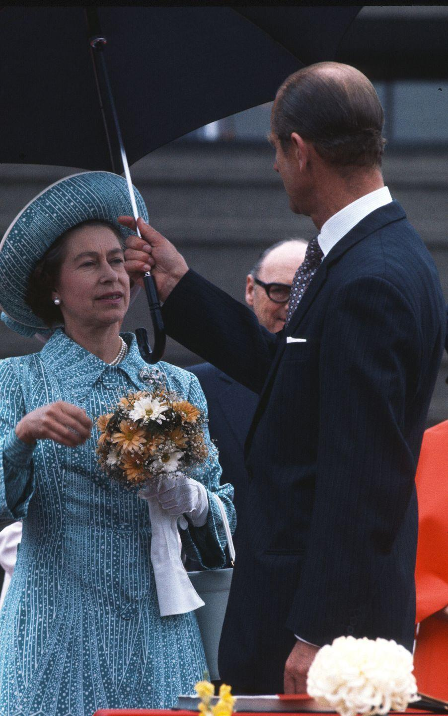 <p>Prince Philip, Duke of Edinburgh, holds an umbrella to shelter the Queen from the rain during their royal tour of Canada in 1976.<br></p>