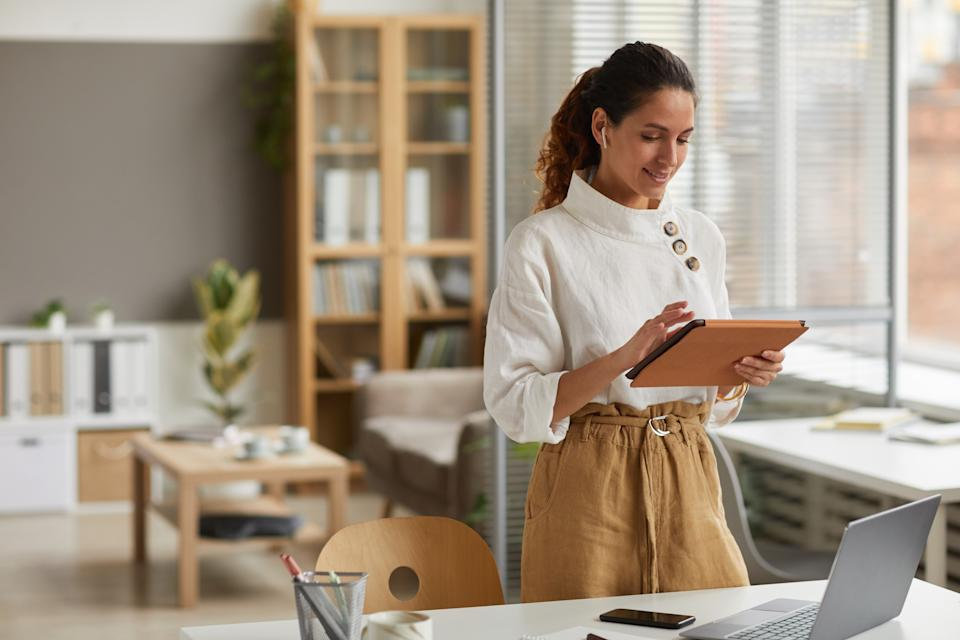 Portrait of elegant businesswoman using digital tablet with wireless earphones while standing by desk in office or at home, copy space