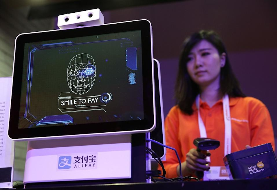 """An Alibaba employee demonstrates """"Smile to Pay"""", an automatic facial recognition payment system at the Alibaba booth at the CES expo in Las Vegas in January 2017. Photo: Getty Images via AFP"""