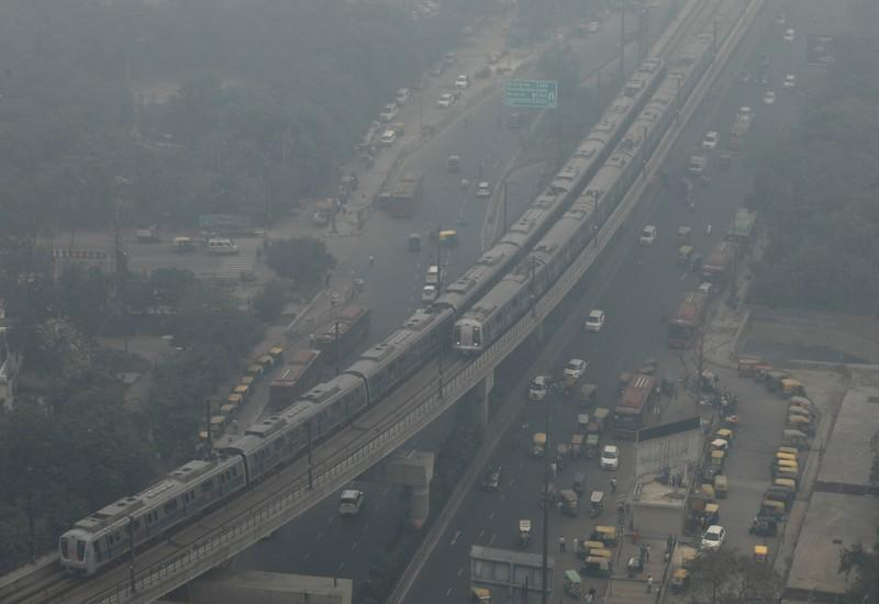 Metro trains move on a foggy morning in Noida on the outskirts of New Delhi