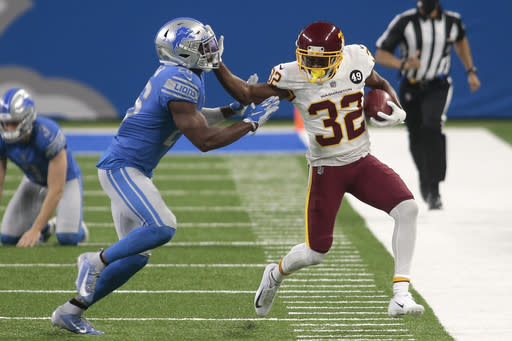 Washington Football Team cornerback Danny Johnson (32) stiff-arms Detroit Lions strong safety Duron Harmon (26) during the first half of an NFL football game, Sunday, Nov. 15, 2020, in Detroit. (AP Photo/Tony Ding)