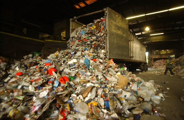 When a recycle truck arrives at the Republic Services of Indiana, its driver has to unload all the recyclable trash to the floor. All kind of trash will be placed on a belt before sending to its sorting house.