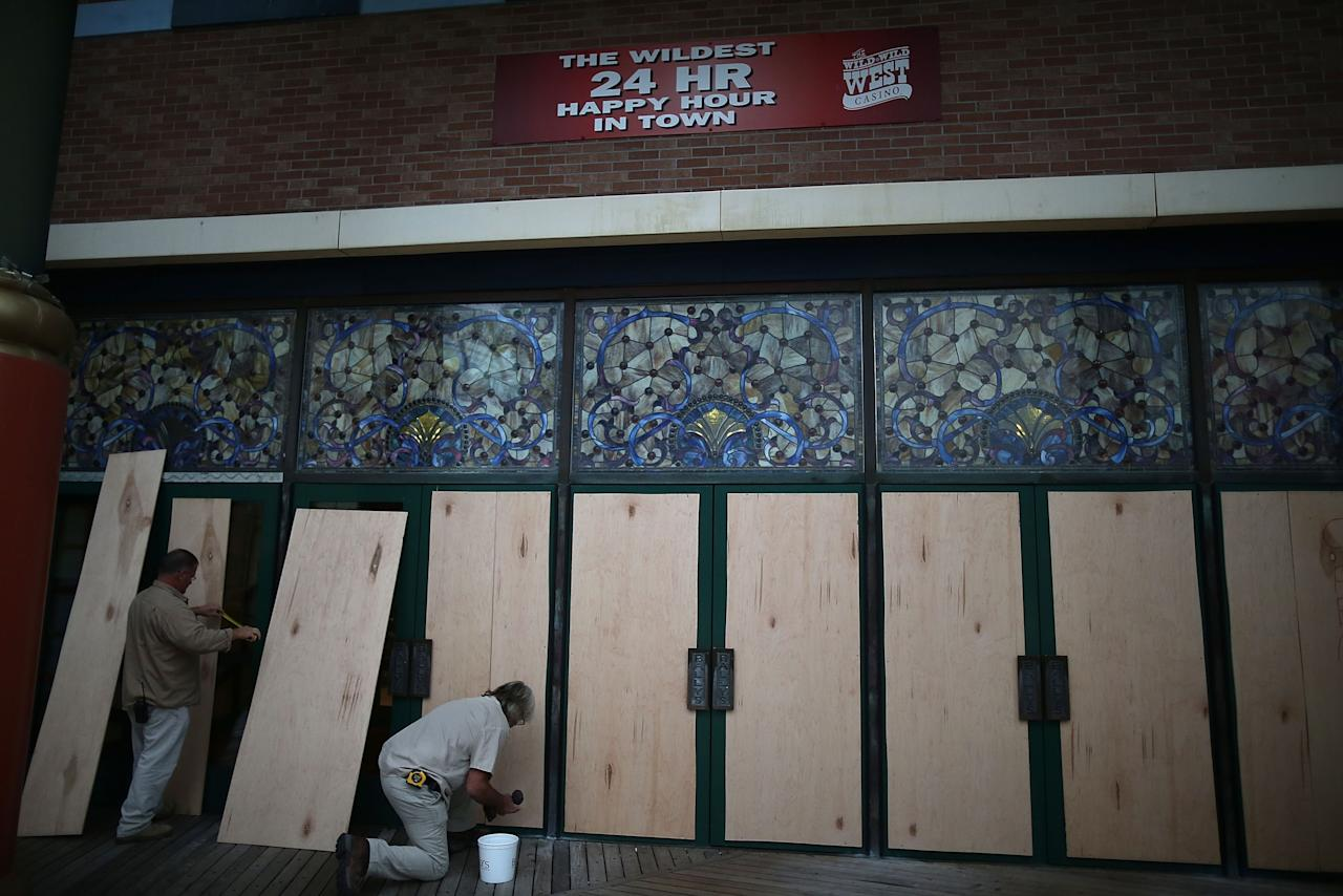 ATLANTIC CITY, NJ - OCTOBER 28: Carpenters Frank Jiacopello (L) and Ron Skinner put plywood over the doors at the Bally's Casino on the boardwalk as Hurricane Sandy approaches on October 28, 2012 in Atlantic City, New Jersey. New Jersey Gov. Chris Christie ordered Atlantic City's 12 casinos to shut down and surrounding states have also declared a state of emergency. Sandy, which has already claimed over 50 lives in the Caribbean, is expected to hit the New Jersey coastline sometime on Monday bring heavy winds and floodwaters.  (Photo by Mark Wilson/Getty Images)