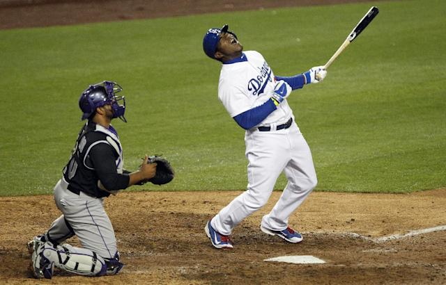 Los Angeles Dodgers' Yasiel Puig, right, reacts to hitting a fly ball for an out to right field with Colorado Rockies catcher Wilin Rosario, left, looking on in the eighth inning of a baseball game on Friday, April 25, 2014, in Los Angeles. (AP Photo/Alex Gallardo)