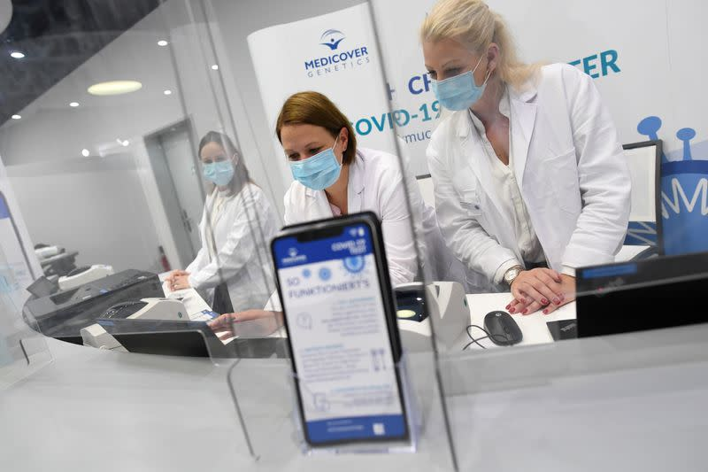 FILE PHOTO: Employees of new COVID-19 quick test center at Franz-Josef-Strauss airport work behind counter in Munich