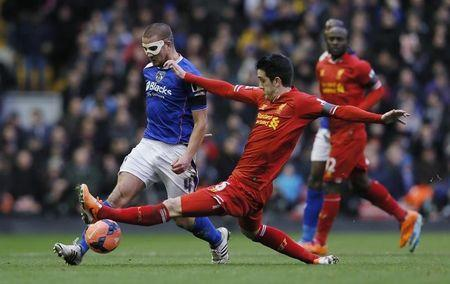 Oldham Athletic's James Wesolowski challenges Liverpool's Luis Alberto during their FA Cup third round soccer match at Anfield in Liverpool January 5, 2014. REUTERS/Phil Noble