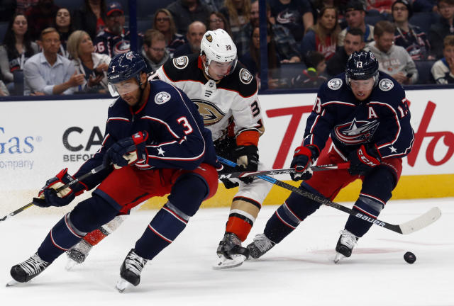 Anaheim Ducks forward Derek Grant, center, works between Columbus Blue Jackets defenseman Seth Jones, left, and forward Cam Atkinson during the first period of an NHL hockey game in Columbus, Ohio, Friday, Oct. 11, 2019. (AP Photo/Paul Vernon)