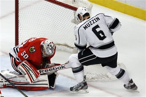 Chicago Blackhawks goalie Corey Crawford (50) gathers in the puck as Los Angeles Kings defenseman Jake Muzzin (6) looks for a rebound during the first period in Game 5 of the NHL hockey Stanley Cup playoffs Western Conference finals, Saturday, June 8, 2013, in Chicago. (AP Photo/Charles Rex Arbogast)
