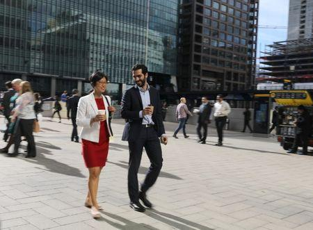 People walk through the financial district of Canary Wharf, London 28 September 2017.