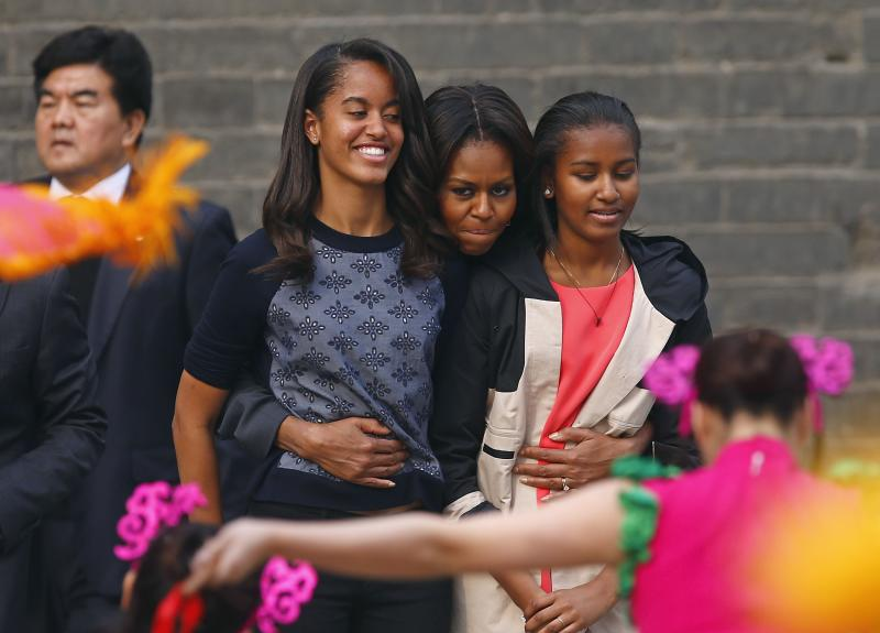 U.S. first lady Michelle Obama (C) hugs her daughters Malia (2nd L) and Sasha (R) as they watch a folk dance by performers during her visit at the City Wall, in Xi'an, Shaanxi province, March 24, 2014. REUTERS/Petar Kujundzic (CHINA - Tags: POLITICS TRAVEL SOCIETY)