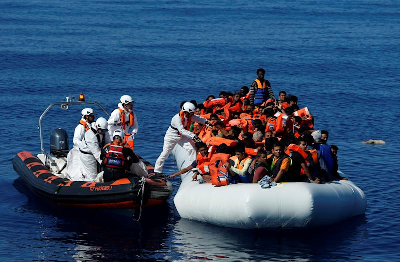 Rescuers from Malta-based NGO Migrant Offshore Aid Station (MOAS) distribute life jackets to migrants on a rubber dinghy in central Mediterranean on international waters off Zuwarah