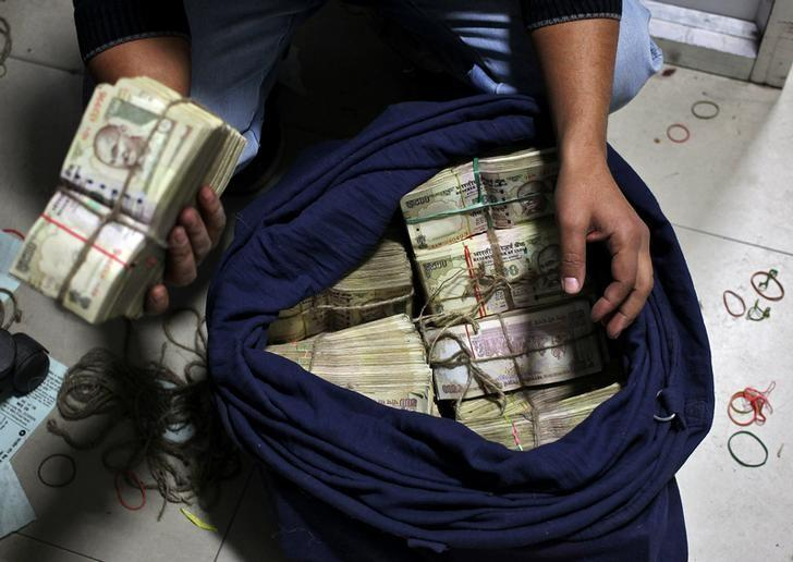 A bank employee takes out a bundle of old 500 Indian rupee banknotes from a sack to count them inside a bank in Jammu