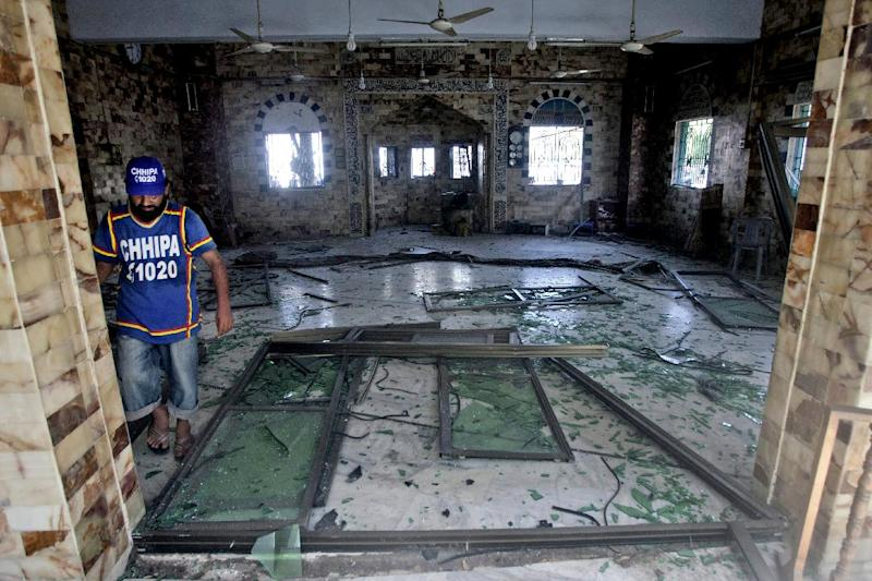 A Pakistani volunteer checks the damage inside a mosque caused by a bomb blast in Karachi, Pakistan, Wednesday, June 26, 2013. A bomb targeting a senior judge in the southern Pakistani city of Karachi wounded him and killed several security personnel on Wednesday, a senior government official said. (AP Photo/Shakil Adil)