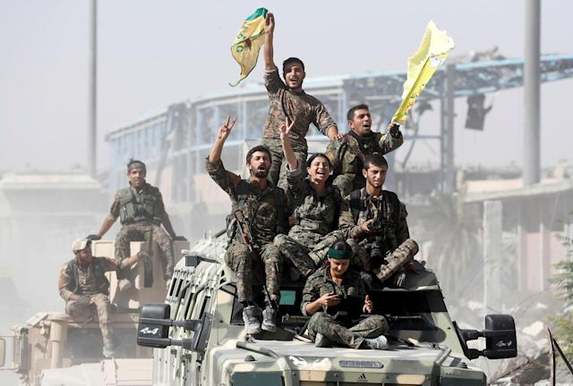<p>OCT. 17, 2017 – Syrian Democratic Forces (SDF) fighters ride atop military vehicles as they celebrate victory against the Islamic State in Raqqa, Syria. (Photo: Erik De Castro/Reuters) </p>