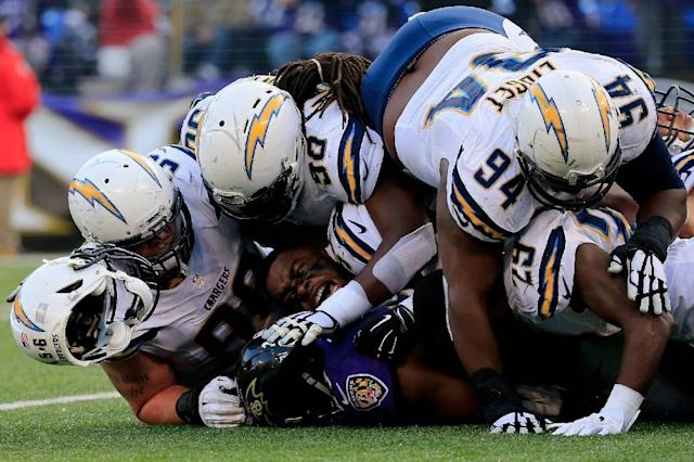 Inside linebacker Donald Butler #56 of the San Diego Chargers loses his helmet while making a tackle on running back Justin Forsett #29 of the Baltimore Ravens at M&T Bank Stadium on November 30, 2014 in Baltimore, Maryland (AFP Photo/Rob Carr)