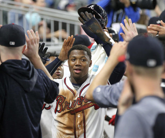 Atlanta Braves Ronald Acuna Jr. gets high-fives in the dugout after scoring on a walk to Tyler Flowers with the bases loaded in the eighth inning of the team's baseball game against the Chicago Cubs on Wednesday, May 16, 2018, in Atlanta. The Braves won 4-1. (Curtis Compton/Atlanta Journal-Constitution via AP)