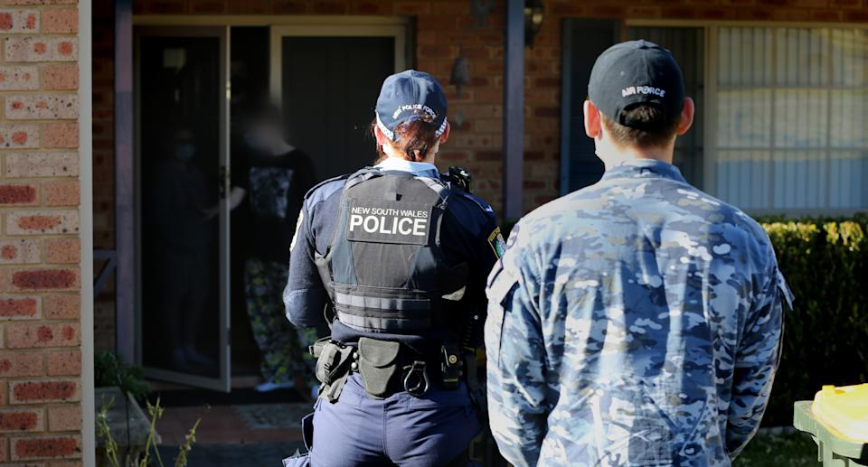 NSW Police and ADF stand in front of a home in western Sydney conducting COVID compliance checks in western Sydney. Source: NSW Police