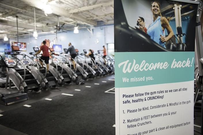 """A """"Welcome Back"""" sign is displayed as people exercise on stairmaster machines at a Crunch Fitness gym location in Burbank, California, U.S., on Tuesday, June 23, 2020. (Patrick T. Fallon/Bloomberg via Getty Images)"""