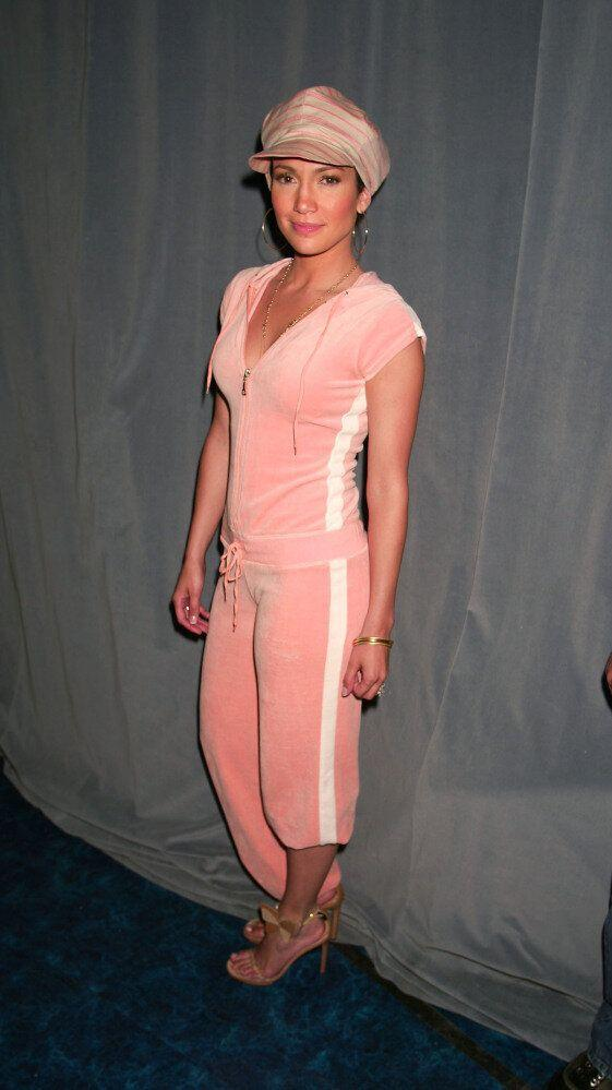American singer and actor Jennifer Lopez stands backstage, wearing a pink tracksuit and cap.
